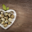 Quail eggs on heart-shaped plate — Stock Photo