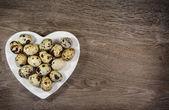 Uova di quaglia su piastra a forma di cuore sul legno — Foto Stock