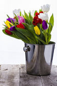 Colorful tulips in metal bucket on the old wooden table — Stock Photo