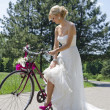 Bride in purple shoes on the bicycle — Stock Photo #23509157