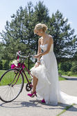 Bride in purple shoes on the bicycle — Stock Photo