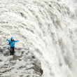 Happy girl standing on a cliff waterfall in Iceland — Stock Photo #23664761