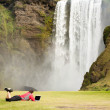 Man with laptop lying on green grass near the waterfall Iceland — Stok fotoğraf