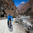 Girl cyclist in the mountains. Annapurna track Himalayas — Stock Photo