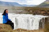 Glückliche mädchen sitzt auf einem felsen-wasserfall in island — Stockfoto