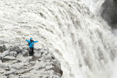 Happy girl standing on a cliff waterfall in Iceland — Stockfoto