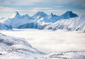 Snowy high mountains of the Alps in the fog — Stock Photo