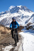 Girl on bike rides in the snow in the high mountains of the HimalayasAnnapurna track Himalayas — Stock Photo