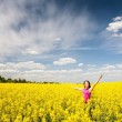Young woman on blooming rapeseed field — Stock Photo