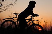 Girl silhouette at sunrise with a bicycle — Stock Photo