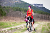 Cyclist girl rides in the mountains — Stock Photo