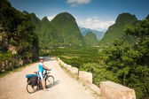 Girl on bike rides on Typical landscape — Stock Photo