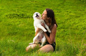 Girl playing with her dog outdoor — Stock Photo