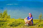Climber sits on a green hill — Stockfoto