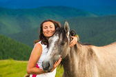 Girl  near a wild horse — Stock Photo