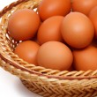 Colored eggs in straw basket — Stok Fotoğraf #23664957