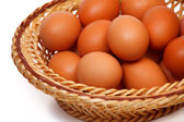 Colored eggs in straw basket — Stock Photo