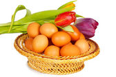 Colored eggs in a basket with tulips — Stock Photo