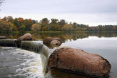 Stone and waterfall against overcast sky in autumn — Stockfoto