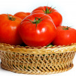 Many tomatoes in a straw basket — Stockfoto