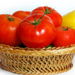 Many tomatoes and pepper in a straw basket — Stockfoto