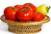 Many tomatoes and pepper in a straw basket — Stock Photo