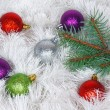 Christmas wreath of tinsel and colored balls with pine branch — Stock Photo #37561899
