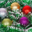 Five Christmas colored balls on the green tinsel — Stock Photo #37561977