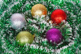 Five Christmas colored balls on the green tinsel — Stock Photo