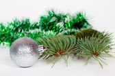 Silvery ball, pine branch and green Christmas tinsel — Stock Photo