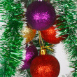 Colored Christmas balls on a green tinsel as a symbol of the New year — Stock Photo
