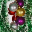 Colored Christmas balls on a green tinsel as a symbol of the New year — Stock Photo #37786177