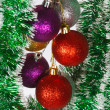 Colored Christmas balls on a green tinsel as a symbol of the New year — Stock Photo #37786349