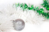 Silvery ball with white and green Christmas tinsel — Stock Photo