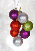 Colored Christmas balls on a white tinsel as a symbol of the New year — Stock Photo