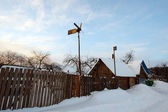 Winter rural landscape with village and vane — Stockfoto