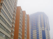 Tall buildings in the fog — Stock Photo