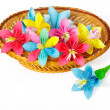 Many colored paper flowers in the basket and one flower near the basket — Stock Photo #41998321