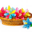 Many colored paper flowers in the basket and one flower near the basket — Stock Photo #41998323