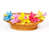 Five colored paper flowers in the basket — Stock Photo