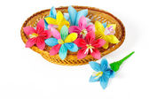 Many colored paper flowers in the basket and one flower near the basket — Stock Photo