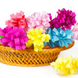 Many colored paper flowers in the basket and one flower near the basket — Stock Photo #42764093