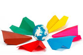 Many colored paper planes and paper globe — Stock Photo