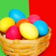 Baked basket with Easter colored eggs on the green and red background — Stock Photo #44652233