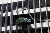 A Green Jaguar car crashed through a multi-story car park. — Stock Photo