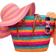 Colorful striped beach bag with a straw hat towel and sunglasses — Stock Photo