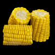 Cooked corn cobs on a black background — Stock Photo
