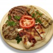 Stock Photo: Mixed grill of pork on wooden mat
