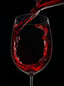 Glass of red wine on black background — Stock Photo