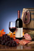 Still life with wine and sausages — Stock Photo